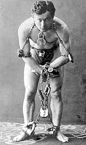 Houdini esposado con cadenas y grilletes.