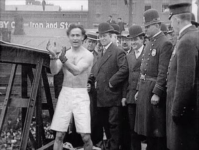 Houdini esposado momentos antes de lanzarse a las frías aguas desde el puente de Weighlock, Nueva York.